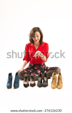 Smiling woman choosing which shoes to put on, studio shot on white background. Choosing the perfect pair of shoes - stock photo