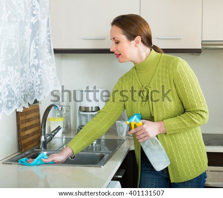 Smiling woman cleaning furniture in kitchen
