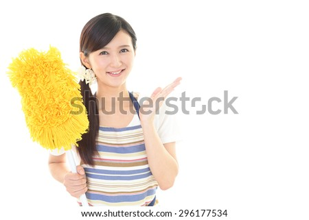 Smiling woman cleaning the house - stock photo