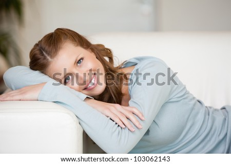 Smiling Woman crossing her arms while lying on a sofa indoor
