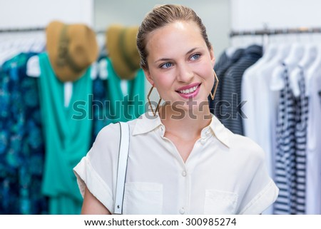 Smiling woman daydreaming in clothing store - stock photo