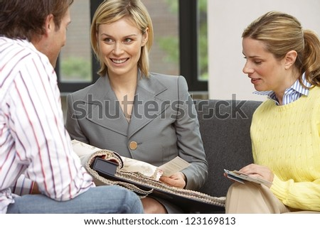 Smiling woman designer holding a large sample book of fabrics assisting a young couple to make their choice