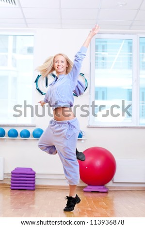 Smiling woman do stretching exercise in sports club. Fitness gym - stock photo