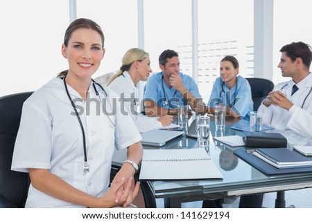 Smiling woman doctor looking at the camera in front of her team during a meeting - stock photo