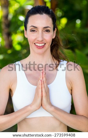 Smiling woman doing yoga on a sunny day - stock photo
