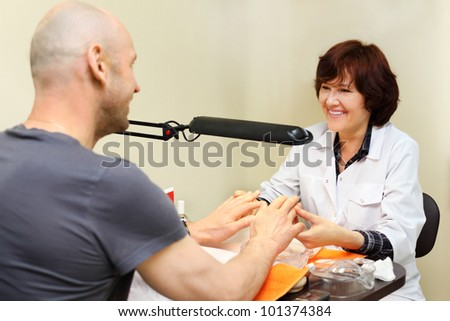 Smiling woman dressed in white coat manicure man in beauty salon - stock photo