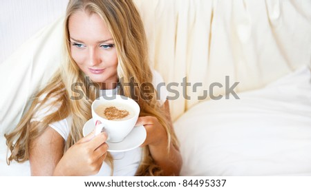 Smiling woman drinking a coffee lying on a bed at home or hotel. Heart shape illustrated on coffee foam. Horizontal shot. Model is looking away. Lots of Copyspace. - stock photo