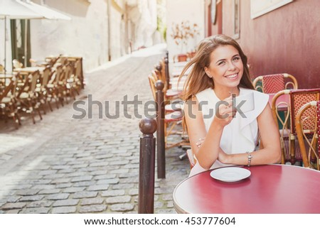 smiling woman drinking coffee in street cafe  - stock photo
