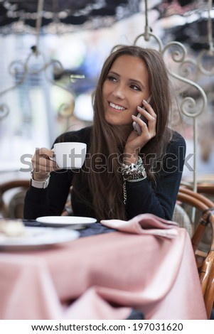 Smiling woman drinking coffee, talking on the phone - stock photo