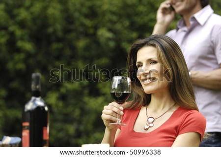 Smiling woman drinking wine in the garden - stock photo