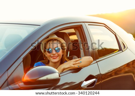 Smiling woman driving a car at sunset. Travel concept - stock photo