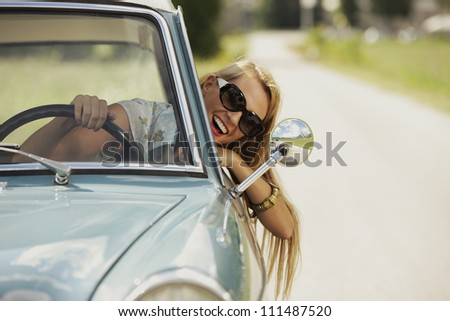 Smiling woman driving vintage car. - stock photo