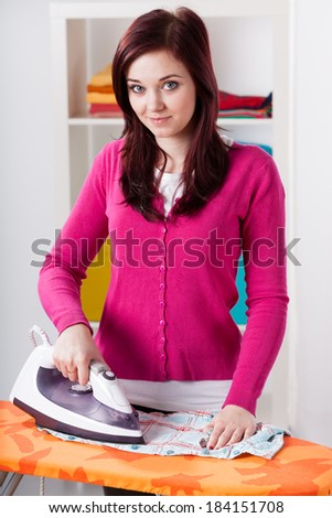 Smiling woman during ironing laundry at home - stock photo