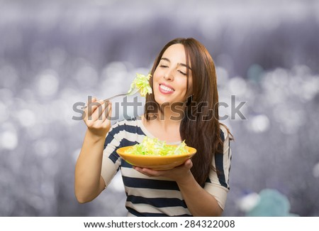 Smiling woman eating a green salad. Over abstract background