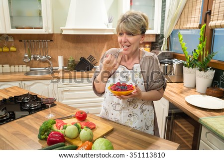 Smiling woman eating berry fruit salad in the kitchen.