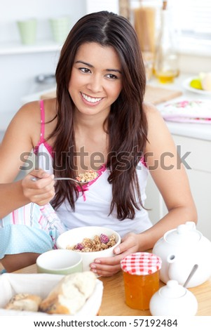 Smiling woman eating muesli with fruits sitting in the kitchen - stock photo