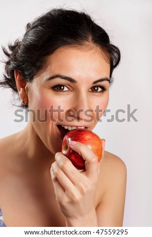 Smiling woman eating red apple - stock photo