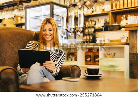 smiling woman enjoying her free time in coffee shop - stock photo