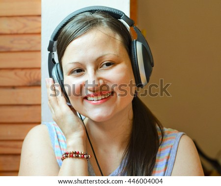Smiling woman enjoys listening to music by headphones. Leisure and happiness concept.