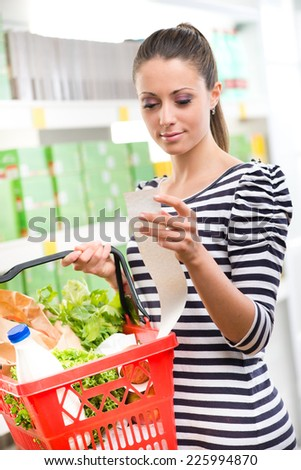 Smiling woman examining a long receipt at supermarket and holding a full shopping basket. - stock photo