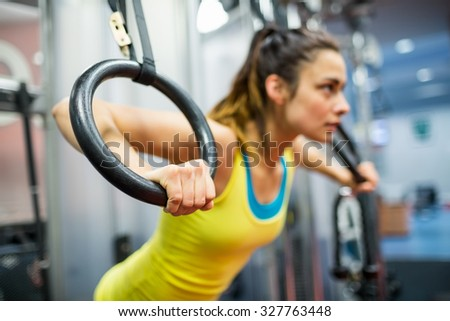Smiling woman exercising her arms at the gym - stock photo