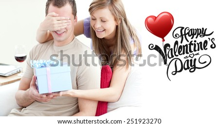 Smiling woman giving a present to her boyfriend against cute valentines message - stock photo