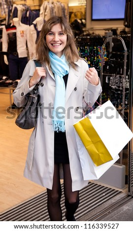 Smiling woman going out of the shop