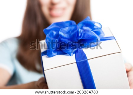 Smiling woman hand holding blue ribbon wrapped holiday surprise gift or present box package - stock photo