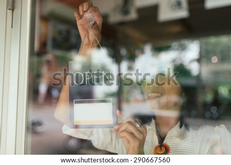 Smiling woman hanging open sign on the glass door - stock photo
