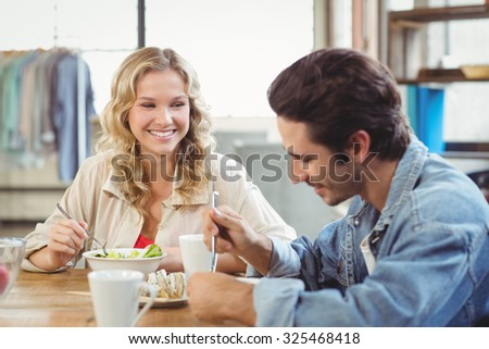 Smiling woman having breakfast with colleague in creative office - stock photo