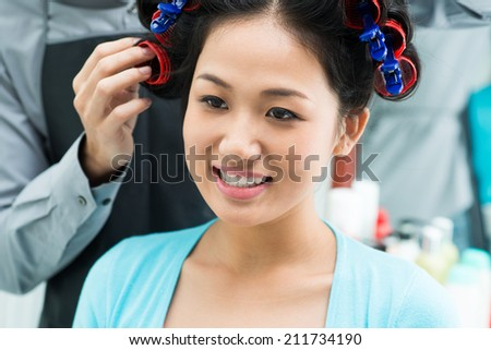 Smiling woman having her hair curled with the rollers - stock photo