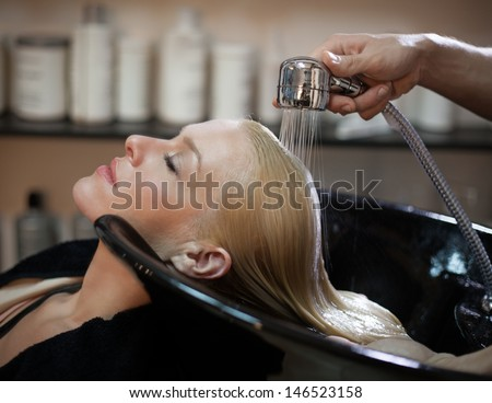 Smiling woman having her hair washed at the hairdresser's. - stock photo