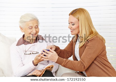 Smiling woman helping senior woman to use her smartphone - stock photo