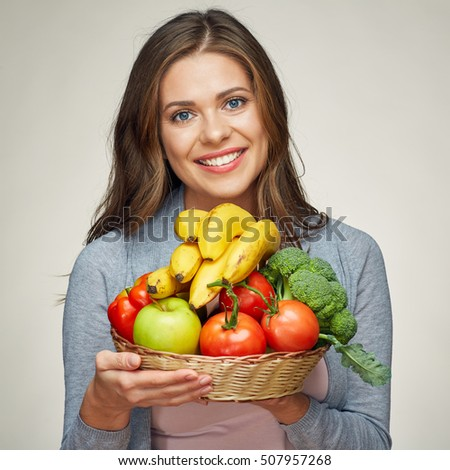 smiling woman hold basket with healthy green food. isolated portrait.