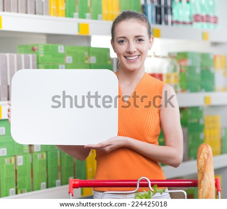 Smiling woman holding a blank sign with supermarket shelf on background. - stock photo