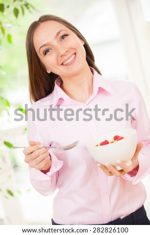 Smiling woman holding a bowl with corn flakes with berries in her hands - stock photo
