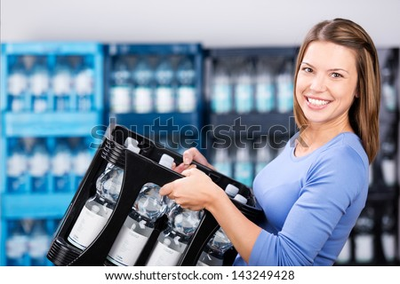 Smiling woman holding a box of refundable bottles - stock photo