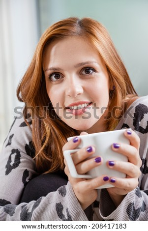 Smiling Woman Holding A Cup Of Coffee And Resting On A Sofa In A Living Room