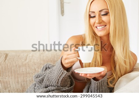 Smiling woman holding a cup of coffee in her living room