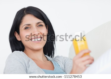 Smiling woman holding a glass of juice in a living room