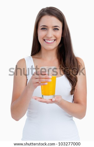 Smiling woman holding a glass of orange juice against a white background