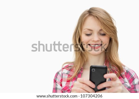 Smiling woman holding a mobile phone against a white background