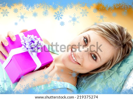 Smiling woman holding a present against snow flake frame in blue - stock photo