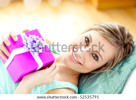 Smiling woman holding a present lying on a sofa