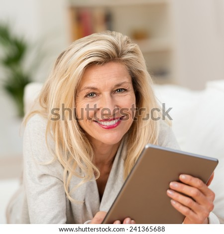 Smiling woman holding a tablet in her hands lying on a sofa in the living room looking at the camera with a wide charming smile - stock photo