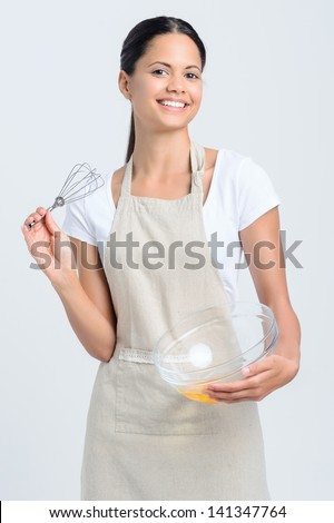 Smiling woman holding a whisk and glass bowl with eggs, ready to bake - stock photo