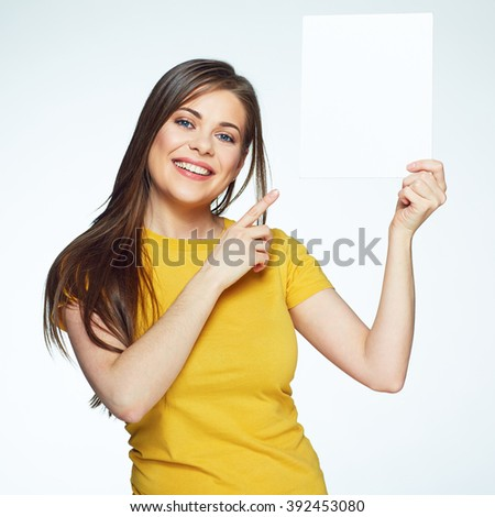 Smiling woman holding advertising sign board. Girl points at White banner. - stock photo