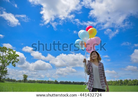 Smiling woman holding balloons in the meadow . - stock photo