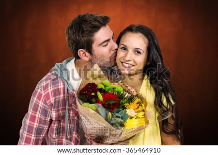 Smiling woman holding bouquet and being kissed by boyfriend against shades of brown - stock photo