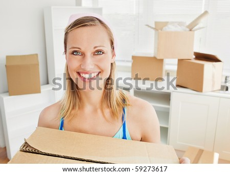 Smiling woman holding boxes after moving looking at the camera - stock photo